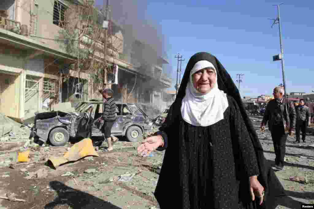 A woman stands near the site of bomb attack in Kirkuk, , Jan. 7, 2014.