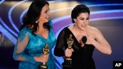 "Rayka Zehtabchi, right, and Melissa Berton accept the award for best documentary short subject for ""Period. End of Sentence."" at the Oscars at the Dolby Theatre in Los Angeles, Feb. 24, 2019."