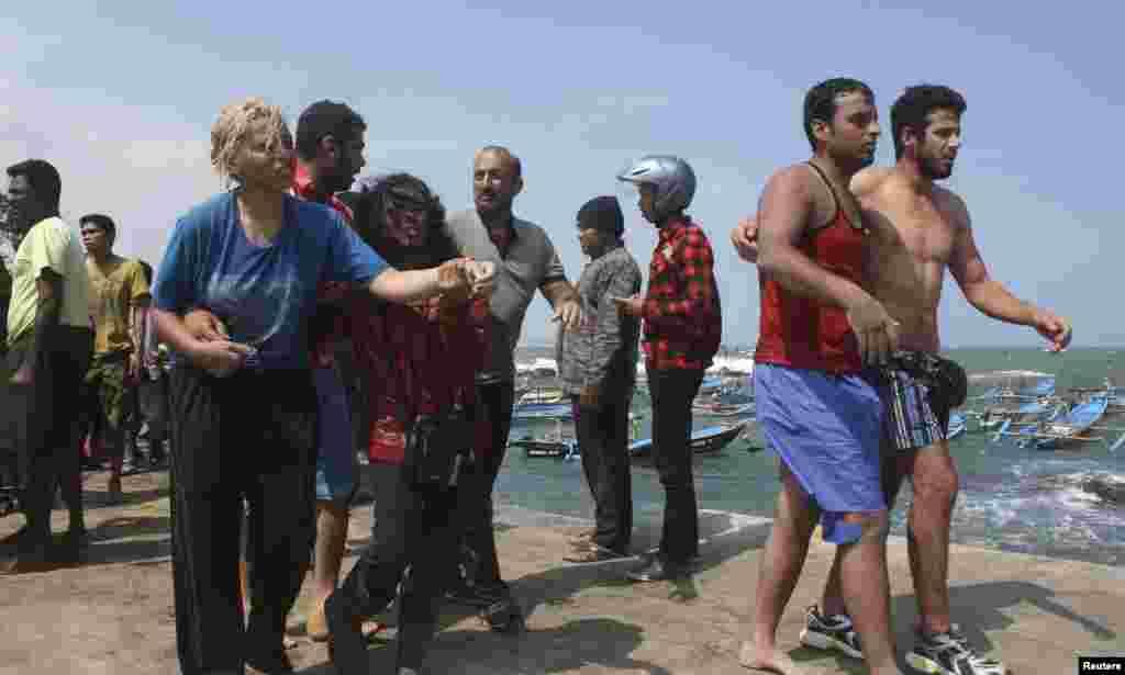 Para pencari suaka yang menumpang kapal yang terbalik setelah menghantam karang di Pantai Jayanti, dekat Cianjur, Jawa Barat (24/7).