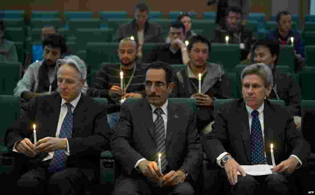 Chris Stevens (à droite), émissaire américain dans la zone sous contrôle des rebelles libyens, l'émissaire britannique Christopher Prentice (à gauche) et le vice-président du Conseil national de transition libyen Abdul Hafiz Ghoqa tenant des bougies lors d'une cérémonie en mémoire du journaliste Tim Hetherington, tué en Libye