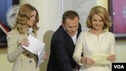 Perdana Menteri Polandia Donald Tusk (kiri) dan istrinya, Malgorzata, memberikan suara mereka selama pemilihan parlemen di Warsawa, Polandia, Minggu (9/10).
