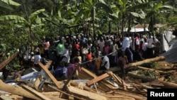 Warga di Desa Nalenda, Uganda berkumpul di sebuah rumah yang hancur akibat bencana tanah longsor di kawasan timur Gunung Elgon (26/6).