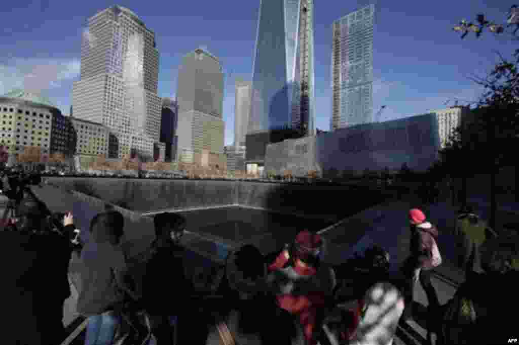 Visitors walk around the National September 11 Memorial, Thursday, Dec. 29, 2011 in New York. The memorial announced that it has had a million visitors since the site opened to the public in September. The museum entrance is at right. (AP Photo/Mark Lenni