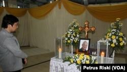 Edu Manik berdoa di depan peti jenazah dan foto temannya Ben Anderson. (VOA/Petrus Riski)