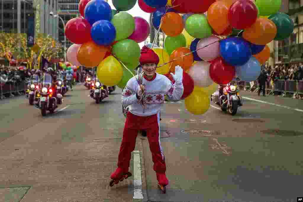 یک شرکت کننده با بالن های رنگارنگ در مراسم رژه جشن روز شکرگزای در نیویورک