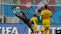 Mexico's goalkeeper Guillermo Ochoa, left, dives to make a save during the group A World Cup soccer match between Mexico and Cameroon in the Arena das Dunas in Natal, Brazil, June 13, 2014.