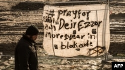 "FILE - A man walks past a banner reading ""Pray for Deir ez-Zor"" at a migrant camp in Calais, France, Dec. 7, 2015. Years of conflict between Syrian government forces and Syrian opposition groups, and the emergence of extremist groups like Islamic State, have forced hundreds of thousands of people to flee from Deir ez-Zor province."