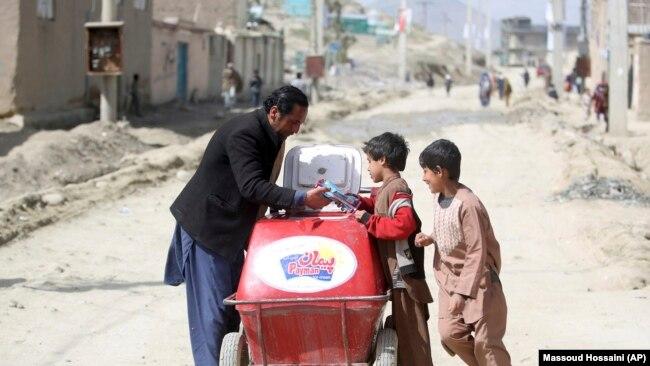 یک کودک افغان همراه با پدرش حین آیس کریم فروشی در یکی از کوچه های کابل