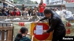 9일 홍콩 중심가에서 시위대가 설치한 바리케이트에 관계자들이 철거 명령 메모를 붙이고 있다.