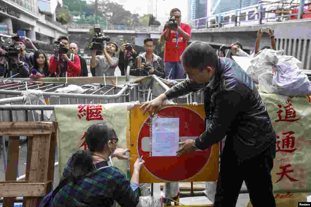 Bailiffs stick an injunction notice on a barricade set up by pro-democracy protesters blocking a main road at the financial Central district in Hong Kong, Dec. 9, 2014.