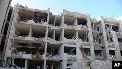 ເຈົ້າໜ້າທີ່ຮັກສາຄວາມປອດໄພຊີເຣຍ ກໍາລັງທໍາການສືບສວນ ເບິ່ງຕຶກໜ່ວຍສຶບລັບກອງທັບອາກາດ ທີ່ໄດ້ຮັບ ຄວາມເສຍຫາຍຈາກການວາງບະເບິດ ນື່ງໃນສອງ ລູກທີ່ແຕກຂຶ້ນໃນກຸງ Damascus (17 ມີນາ 2012)