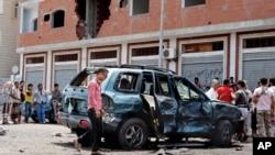 عدن میں مئی 2016 میں ہونے والے ایک خود کش حملے کے بعد لوگ حملے کے مقام پر کھڑے ہیں۔