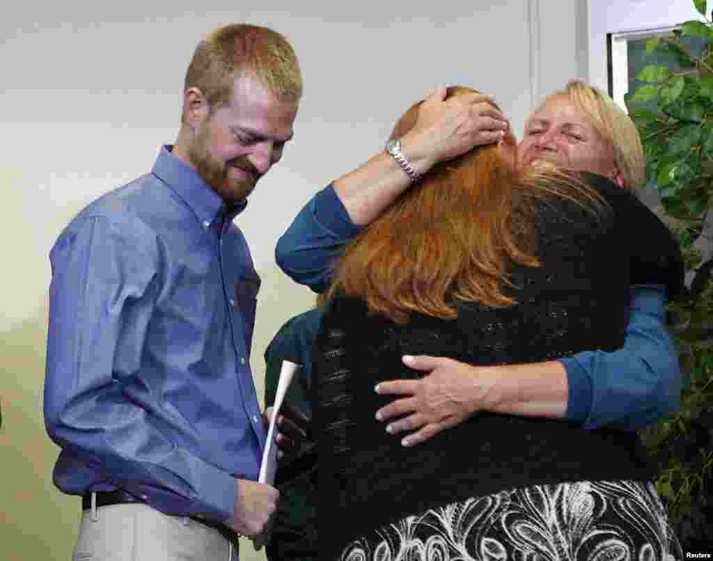 Kevin Brantly (left), who contracted the deadly Ebola virus, looks down as his wife Amber (center) hugs a member of Emory's medical staff during a press conference at Emory University Hospital in Atlanta, Georgia, Aug. 21, 2014.