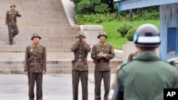 North Korean soldiers look towards the south as a South Korean soldier (R) stands guard in the demilitarized zone separating the two Koreas, July 15, 2011.