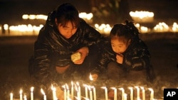 A man and a child light candles during a vigil to honor a Chinese father and his baby shot dead by thieves, in Rome, January 10, 2012.