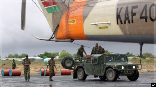 Kenyan troops fuel a supplies helicopter near the Somalia border, Oct. 18, 2011.