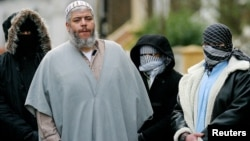 FILE - Muslim cleric Sheikh Abu Hamza (2L) outside the North London Mosque at Finsbury Park.