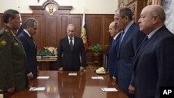 17일 러시아 모스크바 크렘린 궁에서 열린 여객기 추락 사건 관련 회의에 앞서, 블라디미르 푸틴 러시아 대통령(가운데)과 알렉산드르 보르트니코프 연방안보국(FSB) 국장(왼쪽 세번째), 세르게이 라브로프 러시아 외무장관(오른쪽 두번째) 등 각료들이 묵념의 시간을 가지고 있다.