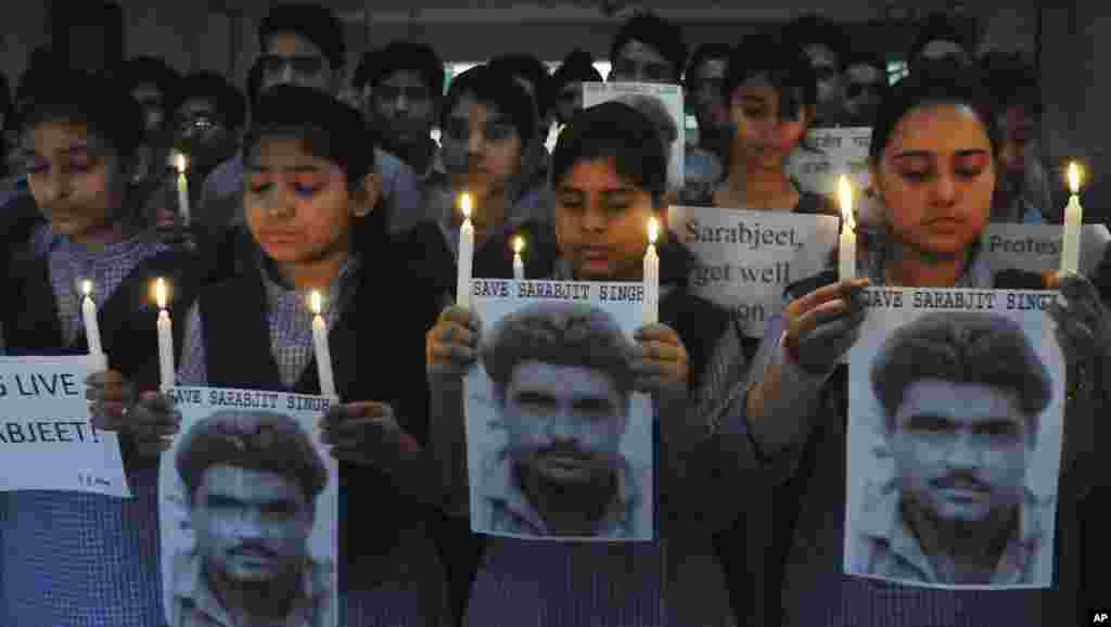 Indian school children hold photographs of Sarabjit Singh, an Indian spy on death row in Pakistan as they light candles and pray for his recovery in Amritsar, India, April 29, 2013.