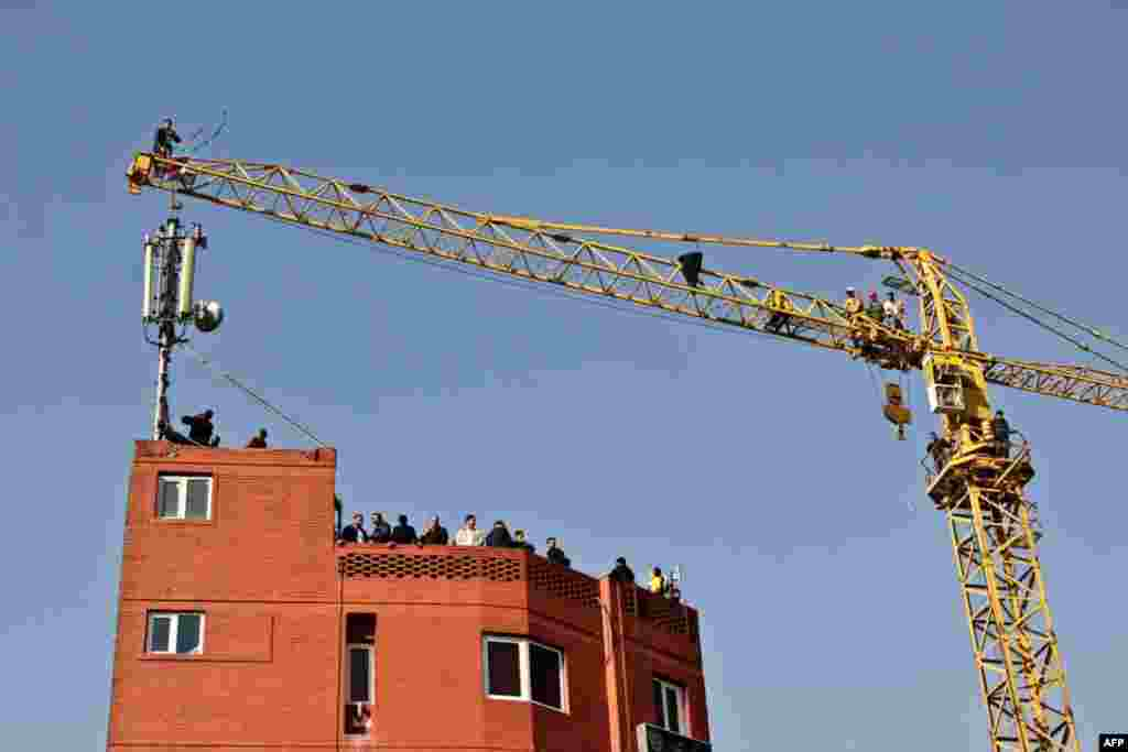A man wearing a green headband stands on top of a crane before attempting suicide in central Tehran