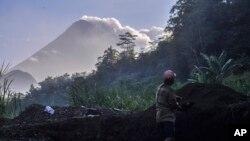 Seorang pria bekerja di tambang galian pasir dengan latar Gunung Merapi, Selasa, 22 Mei 2018. Status Gunung Merapi telah dinaikan menjadi Waspada (level 2), dari Normal (level 1).
