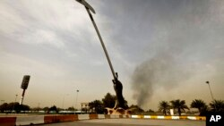 Black smoke from a car bomb attack is seen from the the Crossed Swords monument in Baghad, Iraq, March, 14, 2013.