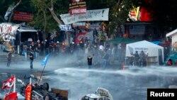 Polisi anti huru-hara membubarkan para demonstran dari Taman Gezi di Lapangan Taksim, Istanbul (15/6). Beberapa jam setelahnya, para demonstran dilaporkan kembali berkumpul di sebuah jembatan kota tersebut.
