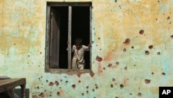 An Indian boy prepares to climb out the window of a house, the walls of which were damaged in mortar shell attack at Jora Farm village, in Ranbir Singh Pura, south of Jammu, India, Feb. 9, 2015.