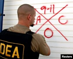 FILE - A Drug Enforcement Administration (DEA) agent marks a house after he searches it for survivors.