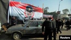 Des officiers de police égyptiens inspectent une voiture, au Caire, le 25 janvier 2014.
