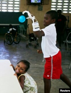Stevenson Joseph (R), practices using a 3D-printed prosthetic hand at the orphanage where he lives in Santo, near Port-au-Prince, April 28, 2014.
