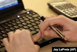 Seorang mahasiswa tengah belajar dengan menggunakan laptopnya. (Foto: AP/Jay LaPrete)