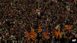 Protesters with ''esteladas'' or Catalonia independence flags pack the University square during a one-day strike in Barcelona, Spain, Tuesday Oct. 3, 2017.
