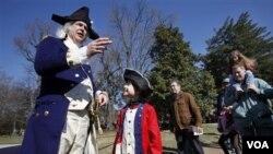 """Lewis Bliss, 10, dari Burke, Virginia, mengenakan pakaian musisi dari masa perang revolusi bertemu dengan """"Presiden George Washington"""", yang diperankan Dean Malissa, dalam acara peringatan ulang tahun presiden pertama Amerika ke-280 di Mount Vernon, di lu"""