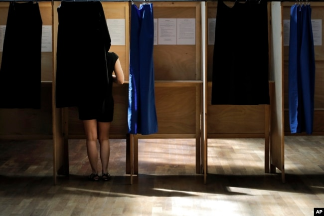 A woman prepares her ballot in a voting booth in the first round of parliamentary elections, in Lyon, central France, June 11, 2017. French voters went to the polls Sunday in the second round to choose lawmakers in the lower house of parliament.