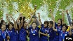 Kapten timnas Jepang Homare Sawa mengangkat trofi Piala Dunia dan disambut rekan-rekannya. Jepang berhasil mengalahkan Amerika Serikat 5-3 lewat adu penalti dalam final Piala Dunia Putri di Frankfurt, Jerman, Minggu (17/7).