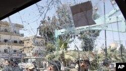 Binh sĩ quân đội Syria bên cạnh chiếc xe quân sự bị hư hỏng sau vụ nổ bom ở thành phố Daraa, miền nam Syria. Vụ nổ nhắm vào các xe tải quân sự Syria hộ tống các thanh sát viên Liên Hiệp Quốc, ngày 9/5/2012