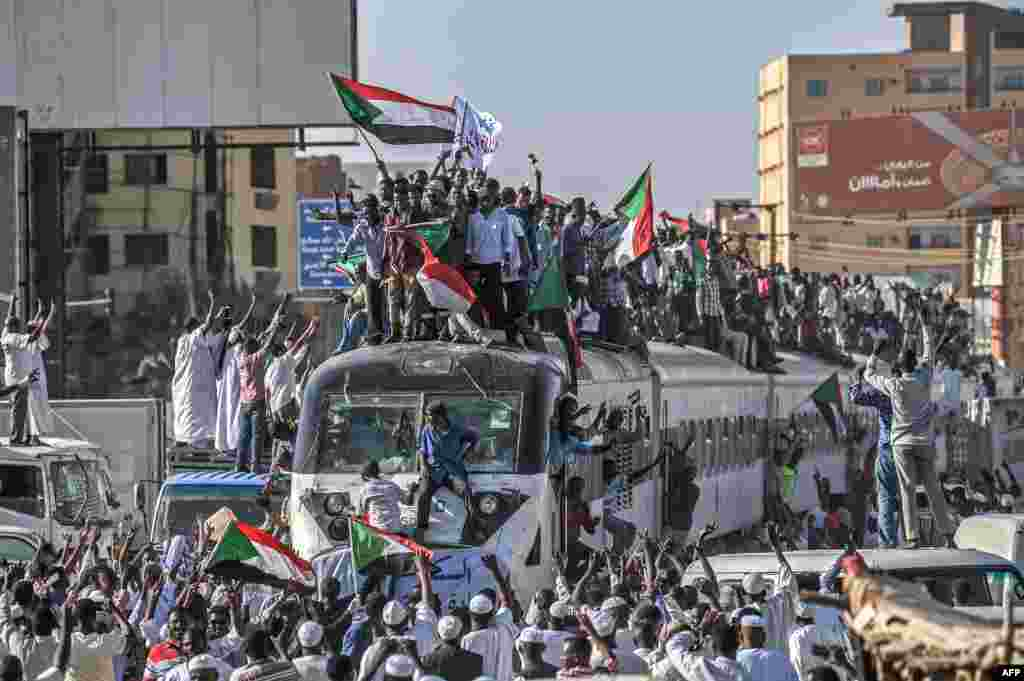 Sudanese protesters from the city of Atbara, sitting atop a train, arrive at the Bahari station in Khartoum. Many protesters perched on the roof of the train, waving Sudanese flags as it chugged through north Khartoum's Bahari railway station before winding its way to the protest site, an AFP photographer said.