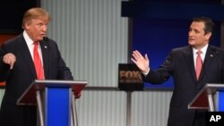 Republican presidential candidate businessman Donald Trump, left, and rival Sen. Ted Cruz, R-Texas, both speak during the Fox Business Network Republican presidential debate at the North Charleston Coliseum, Jan. 14, 2016, in North Charleston, South Carolina.