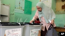An Egyptian casts her vote in the first round of parliamentary elections at polling station in Giza, Cairo, Egypt, Oct. 18, 2015.