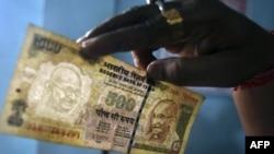 Một nhân viên soi tờ 500 đồng rupee tại 1 quầy thu tiền bên trong 1 ngân hàng ở thành phố Agartala, Ấn Độ, 9/8/2011