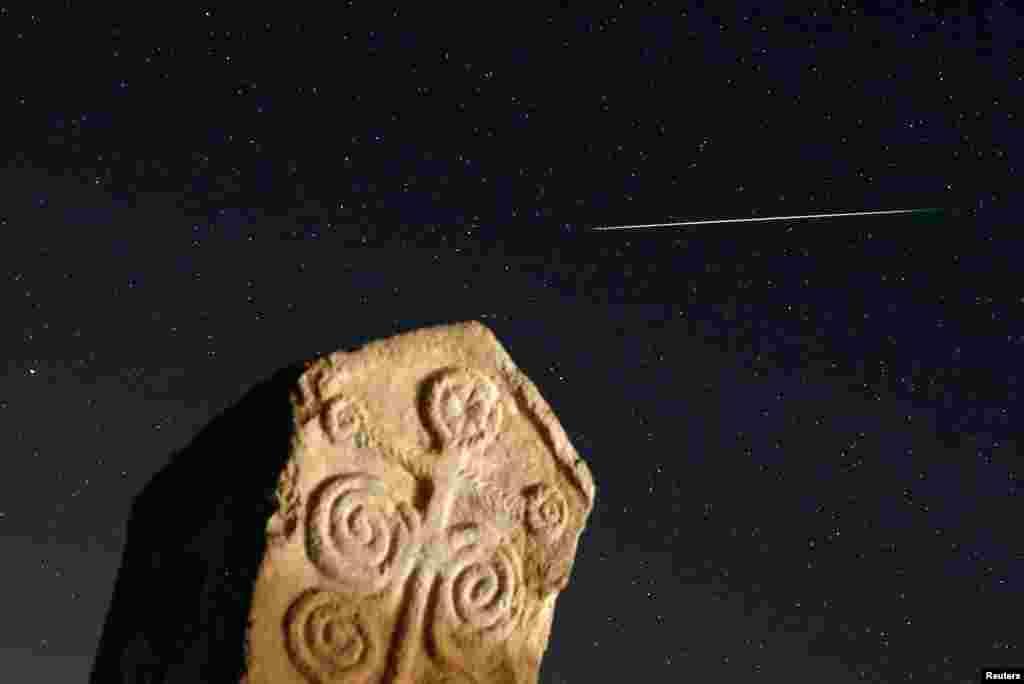 A meteor streaks past stars in the night sky above medieval tombstones in Radmilje near Stolac, south of Sarajevo, Bosnia and Herzegovina.