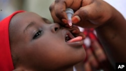FILE - A health official administers a polio vaccine to a child in Kawo Kano, Nigeria, April. 13, 2014.