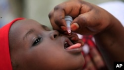 FILE - An unidentified health official administers a polio vaccine to a child in Kawo Kano, Nigeria, April. 13, 2014.