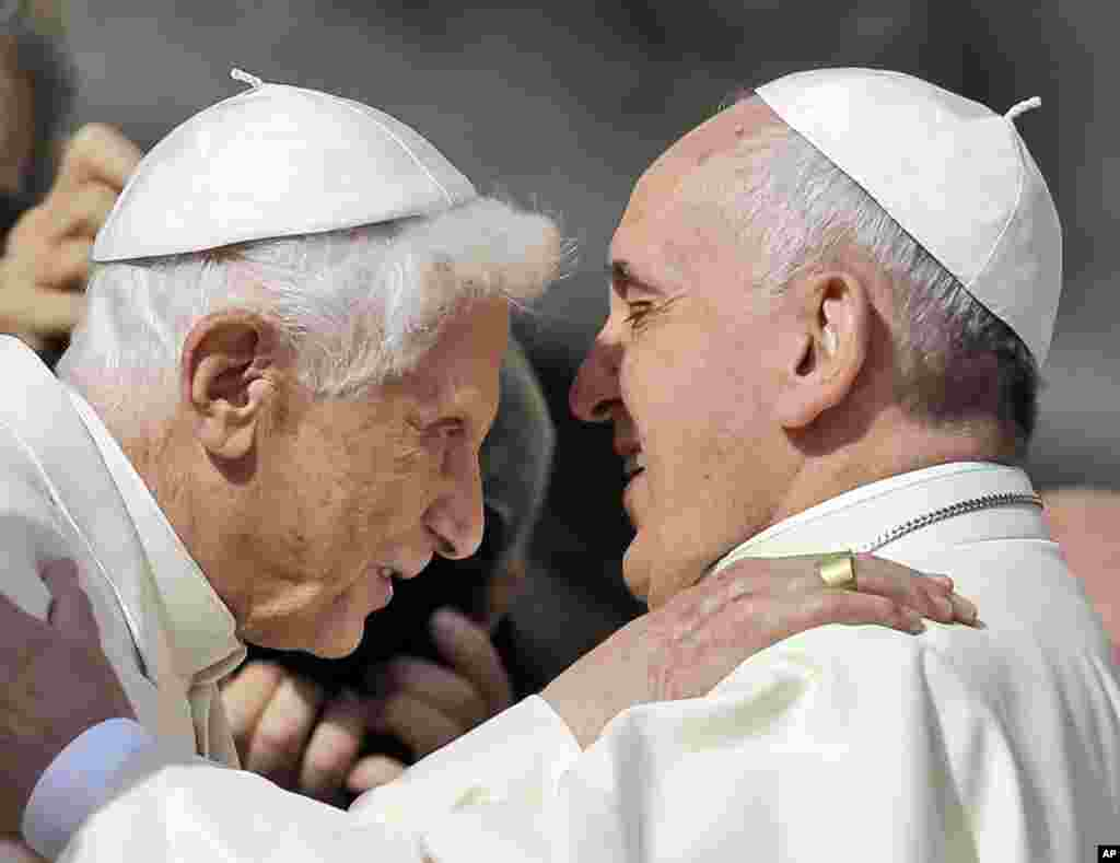 Pope Francis, right, hugs Pope Emeritus Benedict XVI prior to the start of a meeting with elderly faithful in St. Peter's Square at the Vatican.
