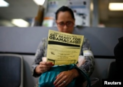 FILE - A woman reads a leaflet on Obamacare at a health insurance enrollment event in Cudahy, California, March 27, 2014. The initiative, launched in 2010 and long scorned by Republicans, has been providing health care coverage to some 20 million previously uninsured Americans.