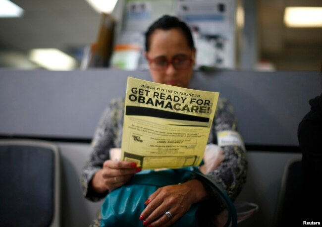 A woman reads a leaflet on Obamacare at a health insurance enrollment event in Cudahy, California, March 27, 2014. The initiative, launched in 2010 and long scorned by Republicans, has been providing health care coverage to some 20 million previously uninsured Americans.