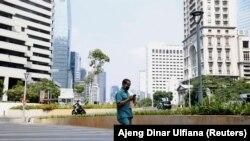 Seorang pria mengenakan masker pelindung wajah, berjalan di kawasan bisnis, Jakarta, Indonesia, 8 Juni 2020. (Foto: REUTERS/Ajeng Dinar Ulfiana)