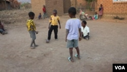 Talandira (in white shirt) plays soccer with friends. (Lameck Masina/VOA)