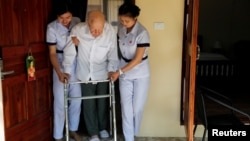 Wolfgang, 96, from Switzerland is helped to walk by two nurses, while staying at the Care Resort in Chiang Mai, Thailand April 6, 2018.